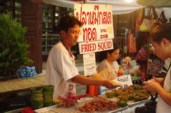 タイビールにも抜群に合いそうな Fried Squid=イカフライの販売屋台。20B 20バーツ。左には屋台のタイ人男性店主。お金を払うお客観光客男性。チェンマイ サタデーマーケット[タイ・チェンマイ旅行(出張)写真ブログの画像]