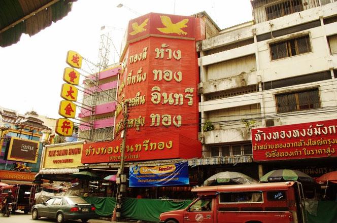 チェンマイのチャイナタウン、ワロロット近郊。華僑の人のお店が多く。中国風の建築。中国の漢字がタイ語と混じっている。パラソルを広げて歩道で営む屋台、露店。手前には赤いソンテウ(乗合タクシーが停車している。)中国の看板には「金行」と書いてある[タイ・チェンマイ旅行(出張)写真ブログの画像]