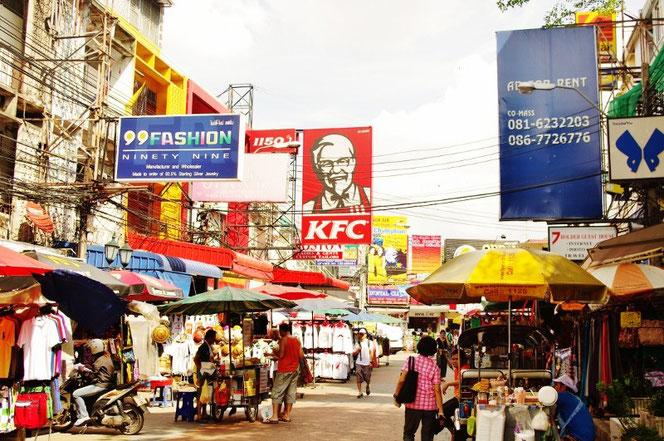 KFC ケンタッキー カオサン店 カーネルサンダースのイラスト看板がタイのカオサンにも。写真両サイドにはパラソルを広げる露天と屋台が広がる。雑多な東南アジアの光景。左側にはごちゃごちゃとした電線も【バンコク ピクチャー】  タイ王国の首都・バンコクの旅行(出張)写真ブログ
