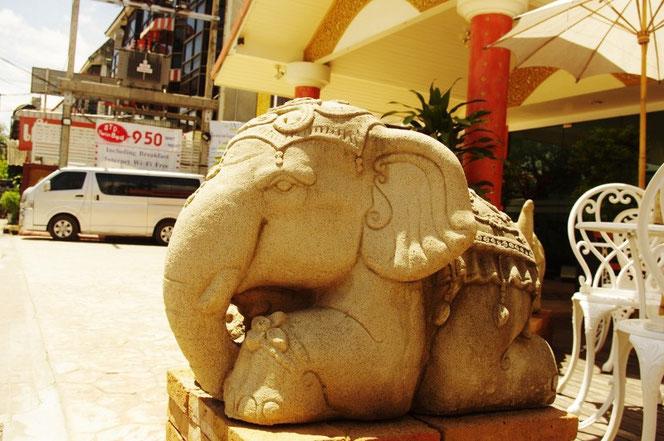 チェンマイのホテル(ゲストハウス)の入り口にある石像の象(ゾウ、エレファント)の写真。伏せ姿で左向き。奥には駐車場、白い車が見える。[タイ・チェンマイ旅行(出張)写真ブログの画像]