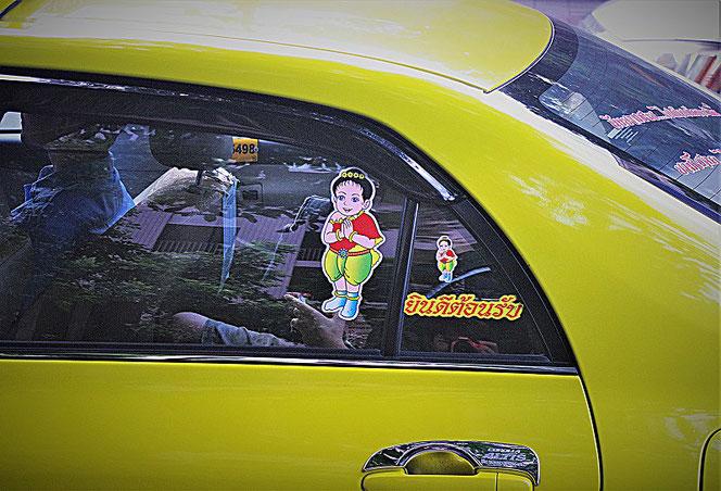 タイ出張旅行時に撮影したバンコクの黄色いタクシーの写真。ガラスに合掌姿のステッカーが貼ってある。思わず笑みが出る。和むタクシーの写真画像。