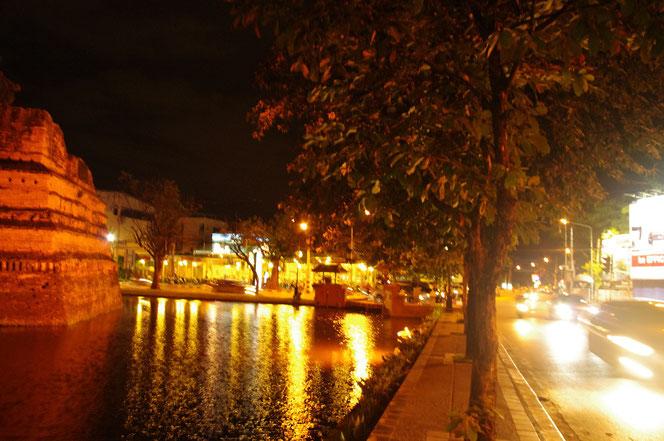 チェンマイ サタデーマーケットの帰り道。お濠の水面に映り込むオレンジ色の街頭の光がゆらゆらと揺れている。幻想的な光景。車は通行するが、歩行者はほぼいないチェンマイの夜の歩道。[タイ・チェンマイ旅行(出張)写真ブログの画像]