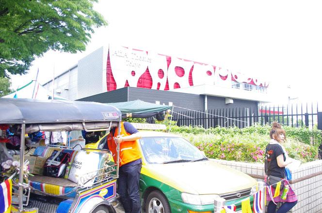 トゥクトゥクのディーラーのスタッフ。TUKTUKの後ろでバンコクのバイクタクシービブスを装着し仕事中。「第14回 タイ・フェスティバル2013年 東京・代々木」の会場写真