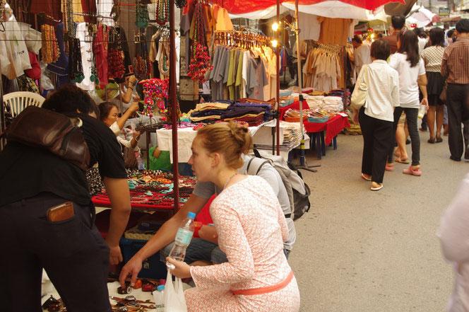 夕方の明るい時間帯のチェンマイ サタデーマーケット。欧米からの若い白人男女カップルがタイ人の男性店員と話す光景。白人女性は薄いピンクのワンピースを着ていてしゃがんでいる。左手にはペットボトルの水。写真奥にはずらりと服飾、雑貨の屋台露店が並ぶ [タイ・チェンマイ旅行(出張)写真ブログの画像]