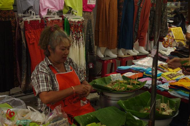 屋台、露店で座りながら食べ物を売る 初老のタイ人女性。エプロン姿。 チェンマイ サタデーマーケット[タイ・チェンマイ旅行(出張)写真ブログの画像]