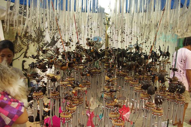 チェンマイ サタデーマーケットで見つけたハンドメイドのウインドチャイム。木彫りの黒いゾウ。金属のベルが付いている。無数に吊り下げられているウインドチャイム、風鈴のタイ雑貨露店、屋台での写真。