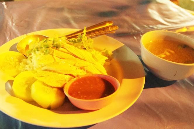 カオマンガイをチェンマイ サタデーマーケットを出た箇所の屋台で注文。白い皿に盛りつけられたカオマンガイ。サービスのスープのお椀が隣にある。[タイ・チェンマイ旅行(出張)写真ブログの画像]