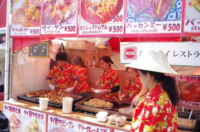 活気のあるレストラン。パッタイ(タイの焼きそば)を鉄板で炒める調理光景。「第14回 タイ・フェスティバル2013年 東京・代々木」の会場写真