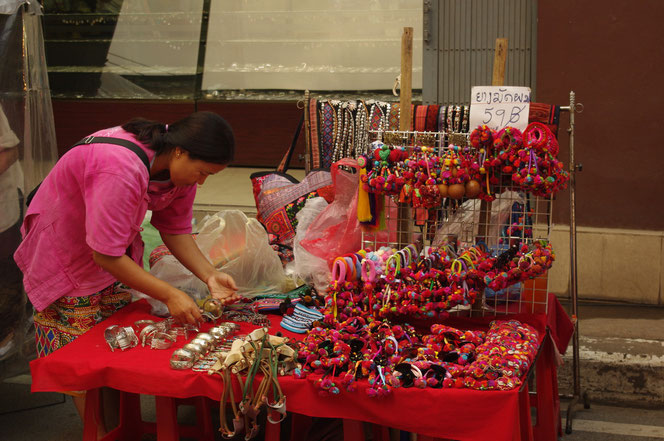 タイの少数民族 モン族?の手製アクセサリー、雑貨小物などを扱うお店。販売光景。店員の女性が仕事をしている。チェンマイ サタデーマーケット[タイ・チェンマイ旅行(出張)写真ブログの画像]
