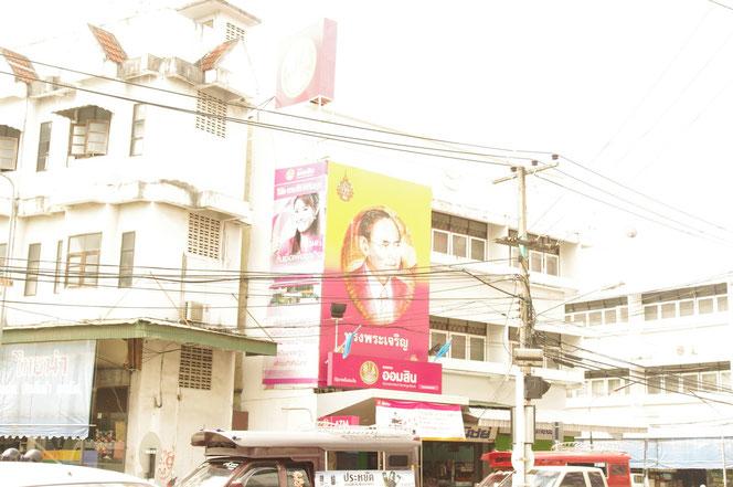 チェンマイにて。タイ国王 ラーマ9世陛下の肖像画。プミポン国王陛下の肖像画を掲げるタイの金融機関、銀行の写真。手前にはチェンマイの乗合タクシー ソンテウが写りこむ。[タイ・チェンマイ旅行(出張)写真ブログの画像]