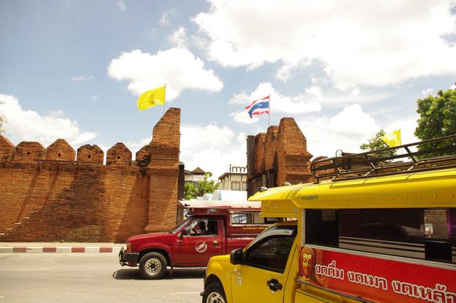 チェンマイのレンガ造りの城壁、門を背景に。ソンテウ(乗り合いバス ピックアップトラック)の赤い車体(直進)、黄色い車体(左折合流)が写る写真。[タイ・チェンマイ旅行(出張)写真ブログの画像]