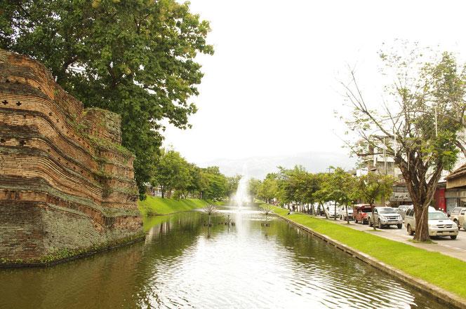 チェンマイの城壁とその手前の水堀の光景。奥には噴水があり、水しぶきを上げている。右側には道路が整備され自動車、ソンテウが通行している。お濠と道路の間には緑の芝生がある。[タイ・チェンマイ旅行(出張)写真ブログの画像]