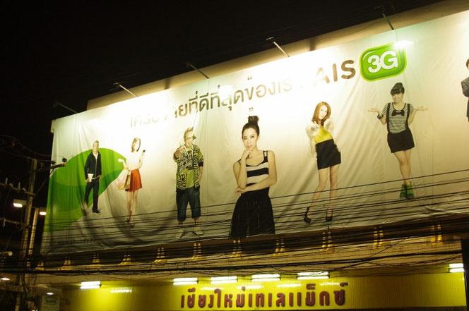 チェンマイ サタデーマーケットからの帰り道。タイの携帯電話会社AIS 3G回線の巨大看板の写真。数名のタイ人モデルたちが思い思いの姿にて、ポージングしている。[タイ・チェンマイ旅行(出張)写真ブログの画像]