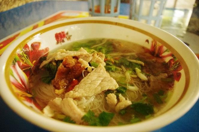 タイの屋台のタイの麺料理(ラーメン)。アップの写真。丼ぶりの中には透き通ったスープ。豚肉、パクチーなどがいろどりを添える。お米でできた細い麺はベトナム料理のフォーと共通している。[タイ・バンコク旅行(出張)写真ブログの画像]