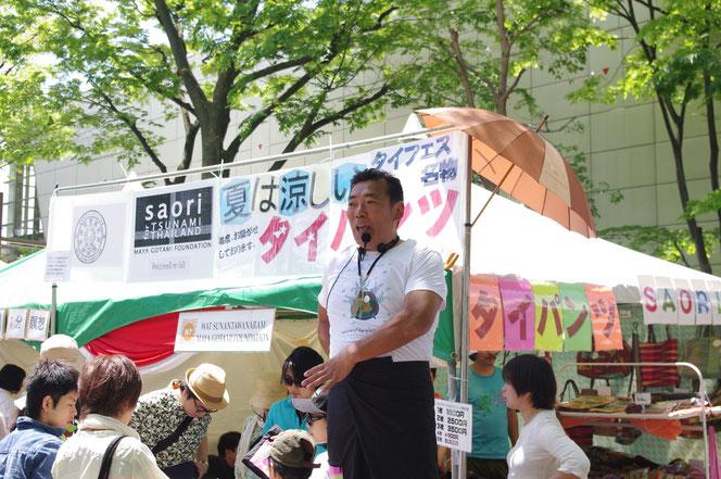 熱心にタイパンツを宣伝、実演販売する販売員の男性。「第14回 タイ・フェスティバル2013年 東京・代々木」の会場写真