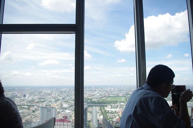 バイヨークスカイホテル。バイヨークスカイレストランのビュッフェ食事中に撮影。ガラス越しの高層階からのバンコクの景色。バンコクの青空と建物、公園なども見える。タイ旅行の絶景の一つ。【バンコク ピクチャー】  タイ王国の首都・バンコクの旅行(出張)写真ブログ