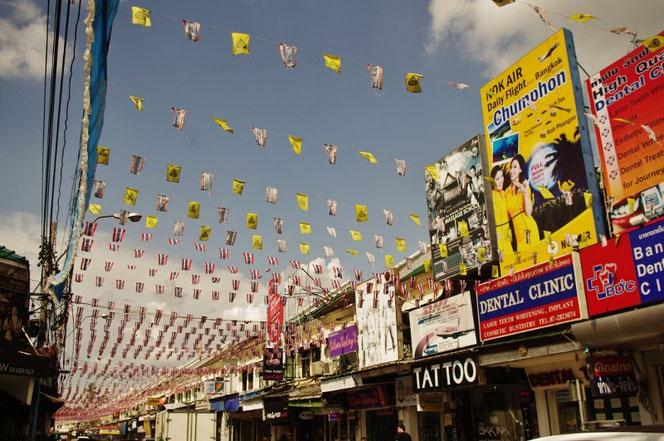 カオサンの写真。空でなびく数えきれないタイと王室の旗。看板にはタイ語だけでなく英語が多く混じる。DENTSAL CLINIC や NOK AIR など 【バンコク ピクチャー】  タイ王国の首都・バンコクの旅行(出張)写真ブログ
