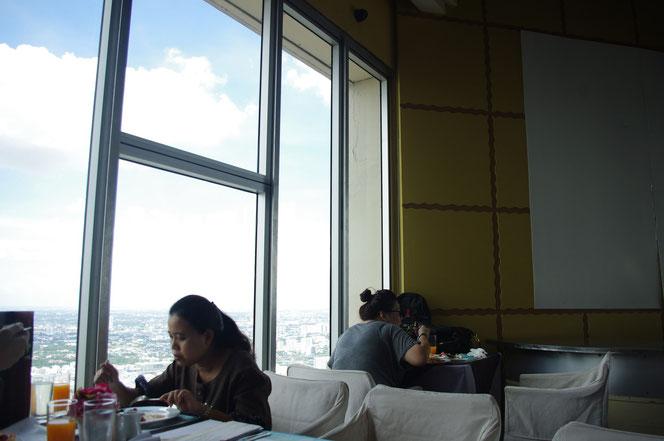 気分はセレブ。バイヨークスカイホテルのスカイレストランのブッフェ。左側には眼下に広がるバンコクの景色が。昼間。青空。食事をするタイ人女性も映る。【バンコク ピクチャー】  タイ王国の首都・バンコクの旅行(出張)写真ブログ