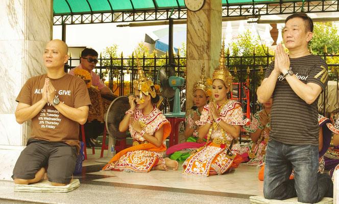 バンコク・エラワン廟(ブラフマー神)に感謝のお祈りをささげるタイ人男性たち。エラワン廟の神事をする女性の光景。合掌姿。[タイ・バンコク旅行(出張)写真ブログの画像]
