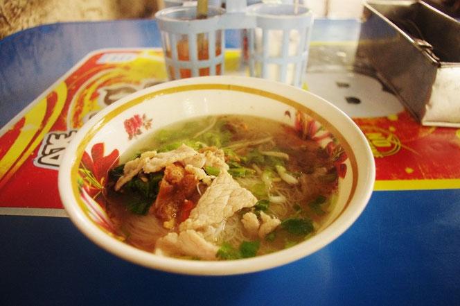 タイの屋台で食べたあっさりとしたラーメン(タイの麺料理)。透き通ったスープ。豚肉、タイの香味野菜が盛り付けてある。麺は米でつくられていて、ベトナムのフォーのよう。屋台のテーブルは青色。麺料理どんぶりの奥には唐辛子などの調味料入れも映る。 [タイ・バンコク旅行(出張)写真ブログの画像]