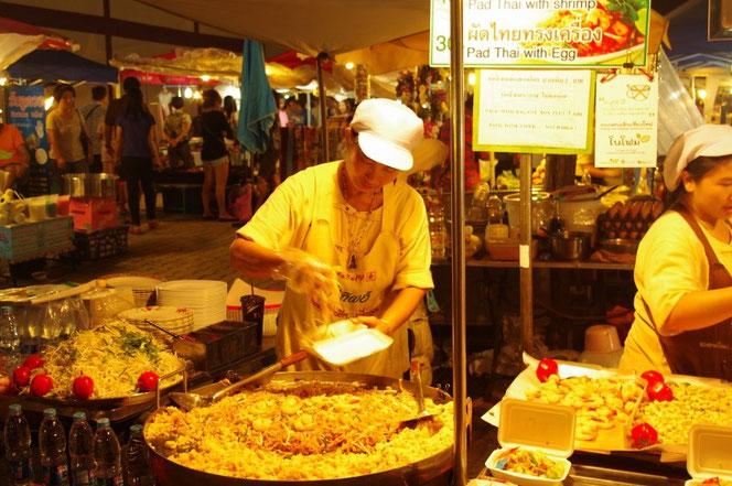 陽が落ちたチェンマイ サタデーマーケット。盛り付けをする食品屋台の女性スタッフ。出来上がったタイ料理を左手のテイクアウト用容器に手際よく盛り付けている。チェンマイ サタデーマーケット[タイ・チェンマイ旅行(出張)写真ブログの画像]
