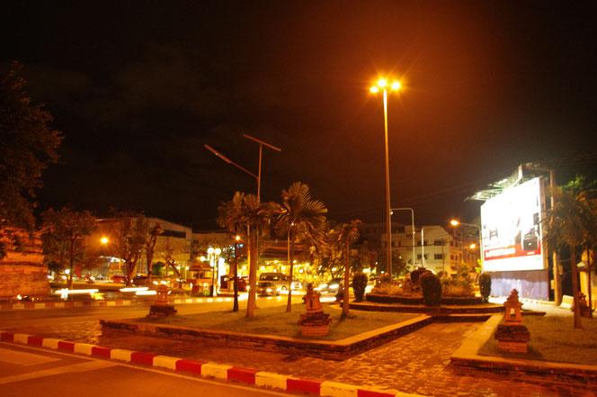 チェンマイ サタデーマーケットの帰り道。閑散とした夜のチェンマイの写真。オレンジ色の街頭が幻想的でどこか優しい雰囲気。歩道には人が誰もいない。場所はチェンマイの北西の城壁、コーナーの箇所。奥には滾々と照らされるプリンターの看板が見える。[タイ・チェンマイ旅行(出張)写真ブログの画像]