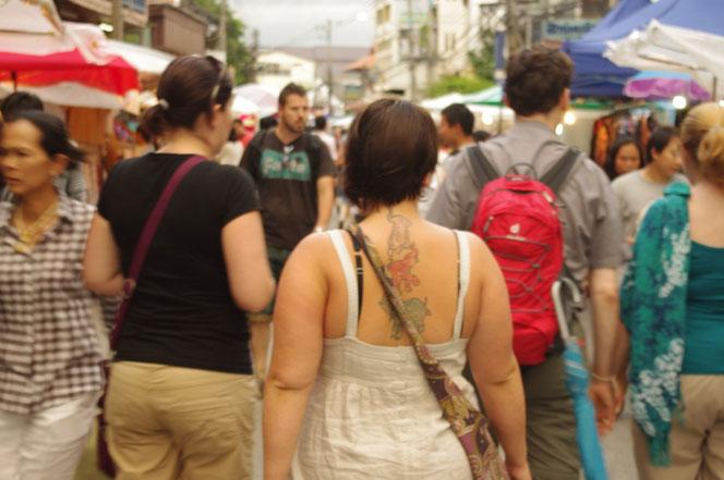 チェンマイ サタデーマーケットの写真。まだ明るい夕方の時間帯。背中に立派なタトゥーを入れたタイ人?のお姉さんの写真が中心。タイ人も多いが、奥には白人男性外国人観光客の姿も。[タイ・チェンマイ旅行(出張)写真ブログの画像]
