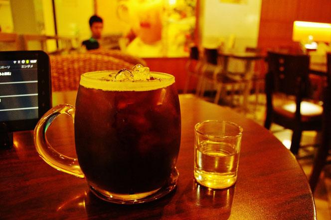 MBK バンコクでのコーヒータイムの写真。ブラックキャニオンコーヒーにて。氷が浮かぶアイスコーヒーのグラスとガムシロップ。ブラウン色のウッドのテーブル。藤でできたチェア。写真左側にはタブレットが映りこむ。画面奥にはカフェでくつろぐ男性が映りこむ。[タイ・バンコク旅行(出張)写真ブログの画像]
