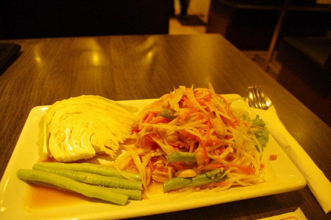 タイ・バンコクのレストランで食べた パパイヤのサラダ(ソムタム)の写真。器の 右側にソムタム。左には生のキャベツが添えてある。スプーンとフォークがペーパーナプキンに包まれている。木目テイストのテーブルで清潔感のあるレストラン。[タイ・バンコク旅行(出張)写真ブログの画像]