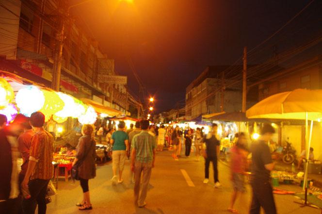 太陽が沈み夜になったチェンマイ サタデーマーケット。遊歩道の光景。中央に道路を歩く人々。両サイドには屋台が。明かりが灯っている。[タイ・チェンマイ旅行(出張)写真ブログの画像]