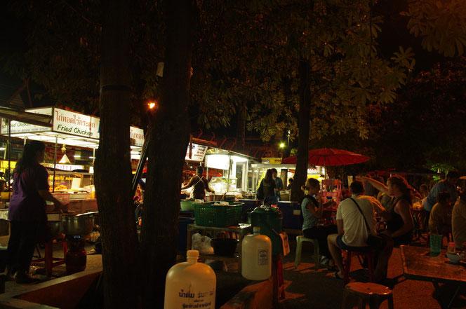 サタデーマーケットの通りから出た場所の屋台街の光景。あたりは夜で暗い。簡単なテーブルと椅子が置かれている。外国人観光客の姿も多い。チェンマイ サタデーマーケット[タイ・チェンマイ旅行(出張)写真ブログの画像]