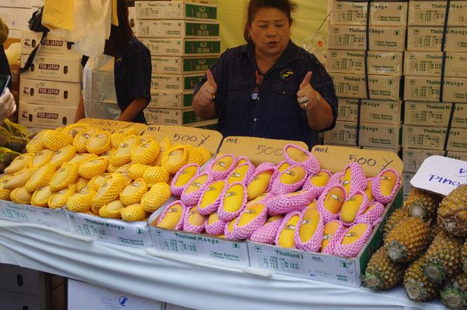 パイナップルにマンゴー。手前に陳列。店員さんの奥にはぎっしりと販売用果物の段ボールが。「第14回 タイ・フェスティバル2013年 東京・代々木」の会場写真
