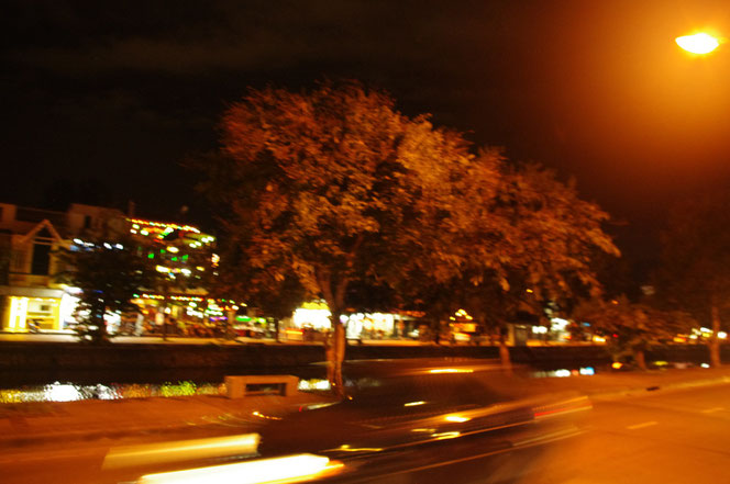 チェンマイ サタデーマーケットの帰り道。夜のチェンマイ市街。スピードを出して走り去る車の写真。高速で走り抜けたため、写真も車がブレてしまっている。写真奥にはチェンマイの水堀も見える。[タイ・チェンマイ旅行(出張)写真ブログの画像]