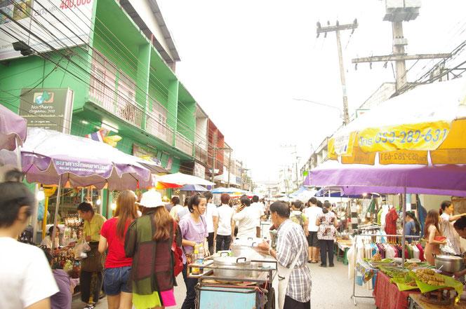チェンマイ門(チェンマイゲート)からのサタデーマーケット入り口の様子 歩行者天国となり 道路中央には観光客や地元の人。両側には大きなパラソルをしたた露店、屋台 雑貨や飲食店、服飾店などが立ち並ぶ [タイ・チェンマイ旅行(出張)写真ブログの画像]