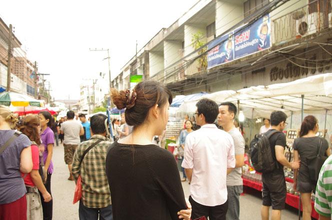 チェンマイサタデーマーケットの 夕方まだ明るい時間。歩行者天国の中央でたたずむ黒い服を着た若い女性。左右には数多くの屋台。白人女性、タイ人以外の外国人も多い。[タイ・チェンマイ旅行(出張)写真ブログの画像]