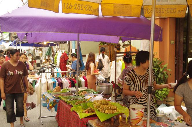 チェンマイ名物のサタデーマーケットを楽しむ地元のタイ人の若い女性。右側にはタイの料理の屋台。奥には服飾の屋台なども連なる。[タイ・チェンマイ旅行(出張)写真ブログの画像]