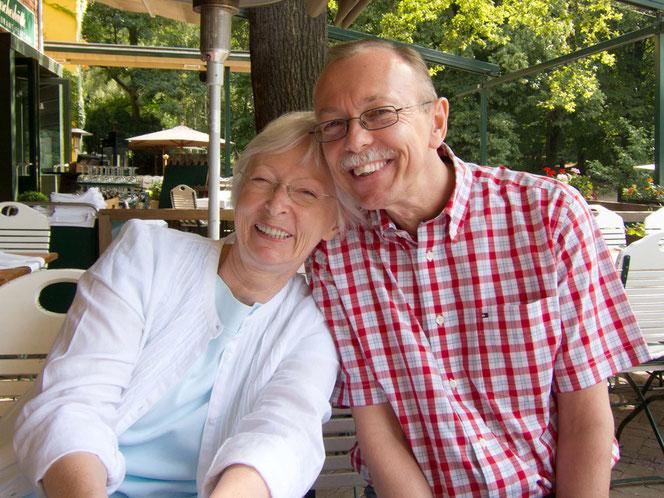 Peter Bach jr. und seine Schwester, Ines-Petra Kaune lehnen in einem Restaurant im Außenbereich nebeneinander gegeneinander. Beide lachen herzlich zum Fotografen. Sie hat ein weißes Outfit an, er ein kurzes rot-kariertes Hemd.