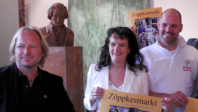 Vorstands-FrauenPower: Gerlinde Steingrüber ist dieses Jahr die Liewerfrau auf dem Plakat; Rudolf Jacobs der Musikant. Da kann Sascha Reichert (li) nur noch tiefschürfend grinsen ... –er malt die Bergischen Motive seit nunmehr 5 Jahren.