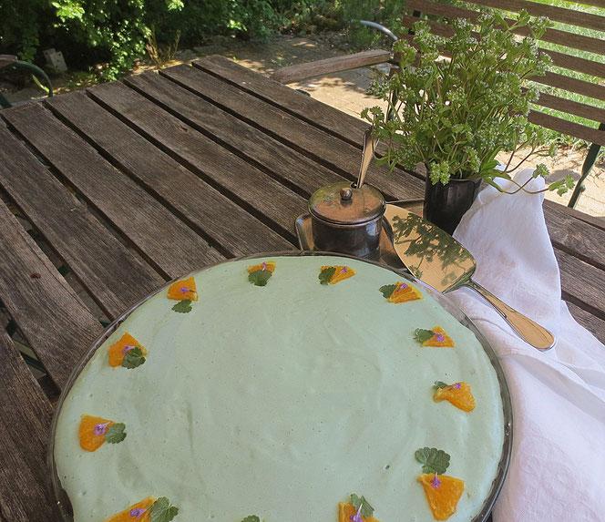 Stillleben mit Waldmeisterkuchen und blühendem Rapunzel im Milchkännchen.