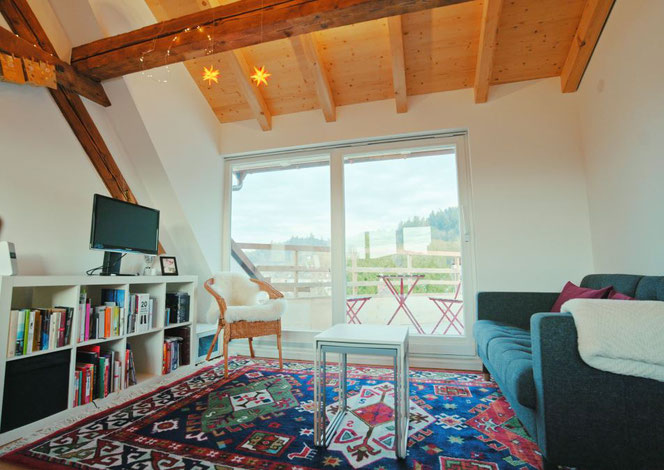 Das Bild zeigt den Wohnbereich mit der Schiebetür zum Balkon