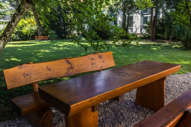 Eine Sitzgruppe aus Baumstämmen geschnitten mit Blick in den Gartenpark