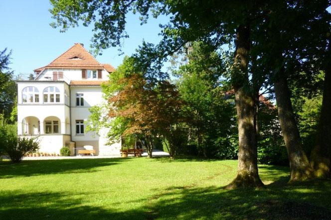 Der Garten des Teutonenhauses an einem sonnigen Tag mit Blick auf das Teutonenhaus