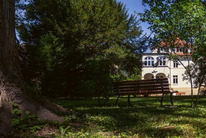 Blick über die Bank im hinteren Teil des Gartens auf das Teutonenhaus