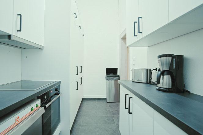 Zweiter Küchenraum mit einem weiteren Kochfeld und dem Backofen sowie den Kühlschränken
