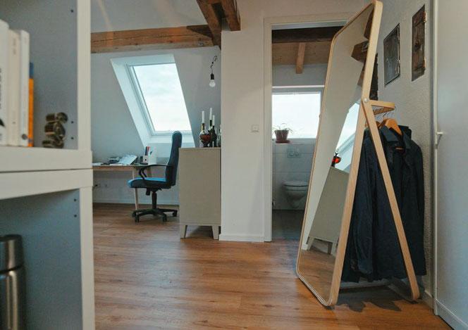 Wir betreten das Zimmer und haben den Blick auf Arbeitspatz und die Tür zum Bad