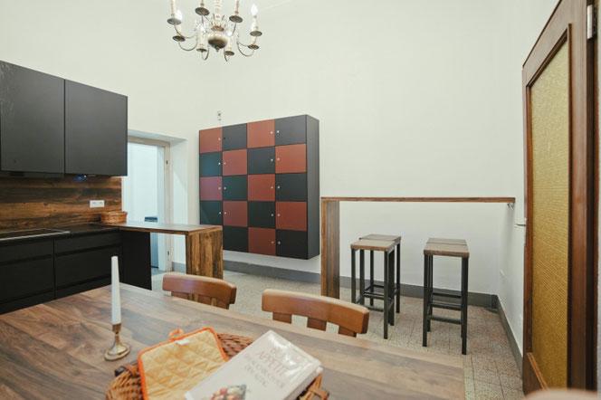 Rechts im Bild der Tresen in der Küche, links die Essensfächer für die Hausbewohner