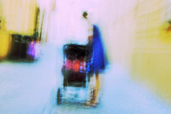 Frau mit Kinderwagen. Kreativ, abstraktes Foto, Aufnahme mit Wischtechnik. Farbgebung durch Crossentwicklung. (RGB)