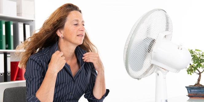 schwitzende Frau sitzt vor einem Ventilator