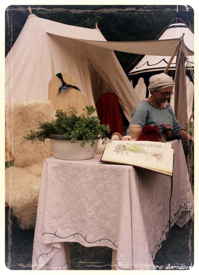 Frau stickt und sitzt an einem Tisch beim Mittelalterfest auf Burg Vondern.