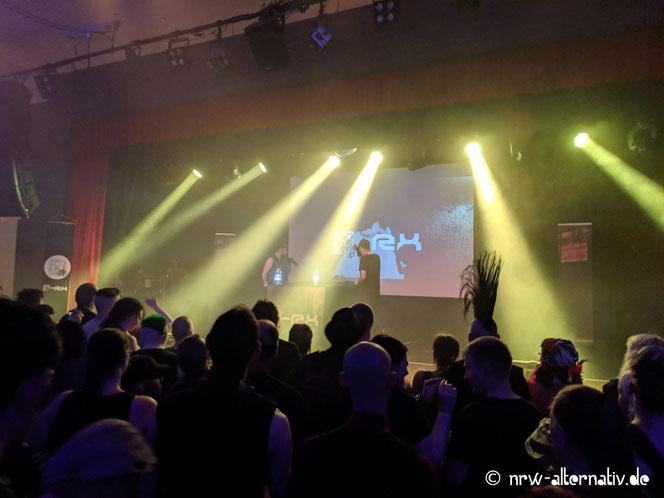 Auf diesem Bild sieht man Menschen vor einer Bühne, auf der die Musiker von X-RX stehen.